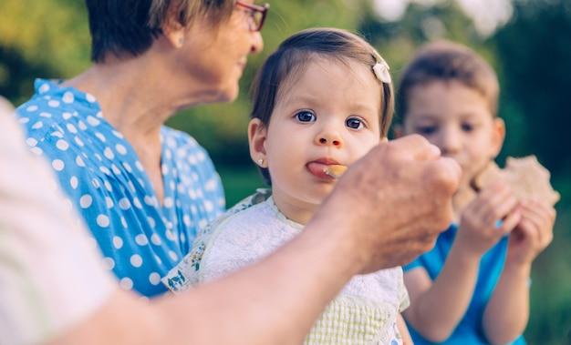 屋外のベンチで年配の女性の上に座っている愛らしい女の赤ちゃんにフルーツピューレを食べている年配の男性のクローズアップ。祖父母と孫のライフスタイルの概念。