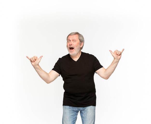 白い背景に分離された空の黒いtシャツで年配の男性の体のクローズアップ。