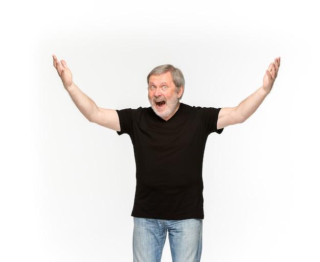 白で隔離される空の黒いtシャツで年配の男性の体のクローズアップ。