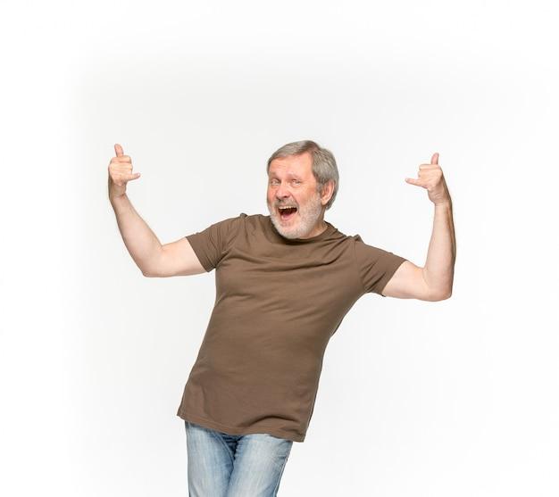 白い背景に分離された空の茶色のtシャツで年配の男性の体のクローズアップ。