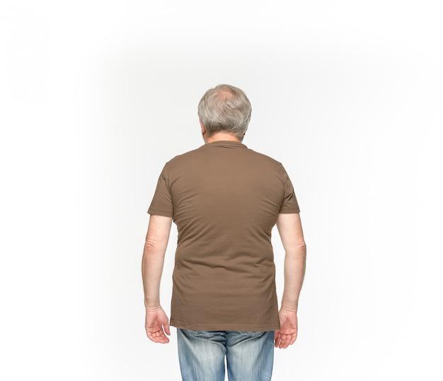白で隔離される空の茶色のtシャツで年配の男性の体のクローズアップ