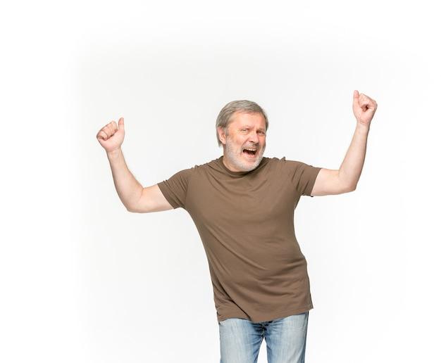 白で隔離される空の茶色のtシャツで年配の男性の体のクローズアップ。