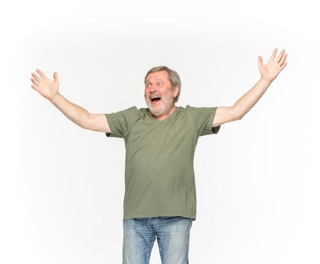 白い背景に分離された空の緑のtシャツで年配の男性の体のクローズアップ。