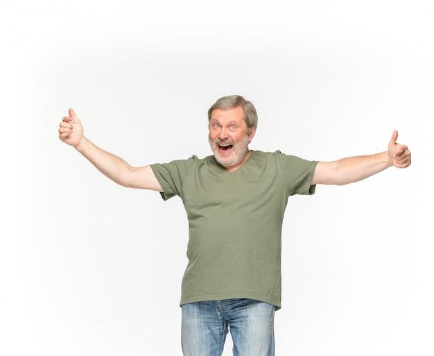 白の空の緑のtシャツで年配の男性の体のクローズアップ。