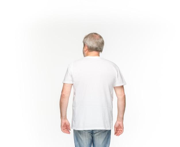 白い背景に分離された空の白いtシャツで年配の男性の体のクローズアップ。服、コピースペースのデザインコンセプトのモックアップ。