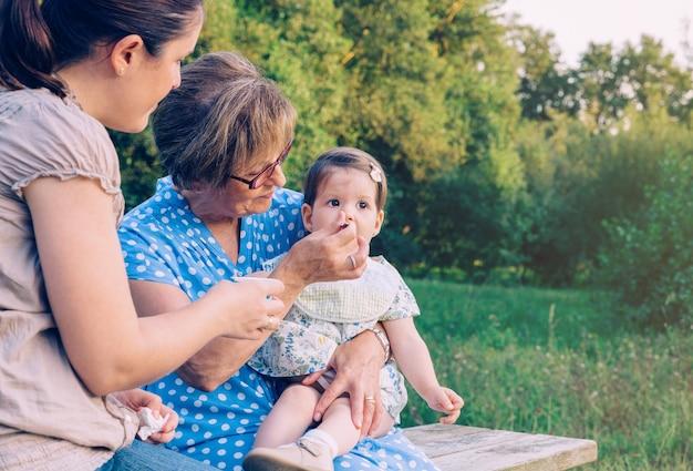 屋外のベンチに座っている愛らしい女の赤ちゃんにフルーツピューレを食べている年配の女性のクローズアップ。 3つの異なる女性世代のコンセプト。