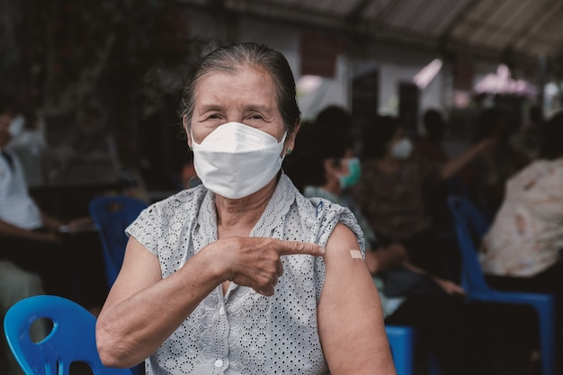 수석 여성의 근접 촬영은 붕대로 어깨를 가리키는 코로나바이러스 covid19 예방 접종을 하러 갔다