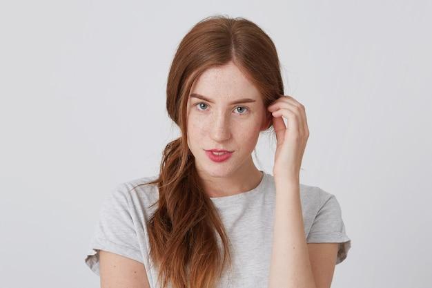 赤い髪とそばかすが立っている官能的な美しい若い女性のクローズアップ