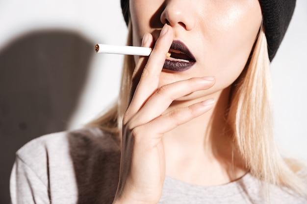 Крупный план чувственной молодой женщины с сигаретой черной помады куря