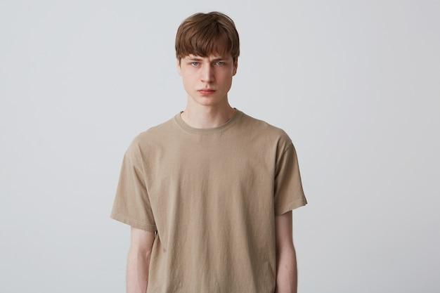 Крупным планом серьезный сердитый молодой человек в бежевой футболке стоит, чувствует себя расстроенным и смотрит вперед, изолированно от белой стены