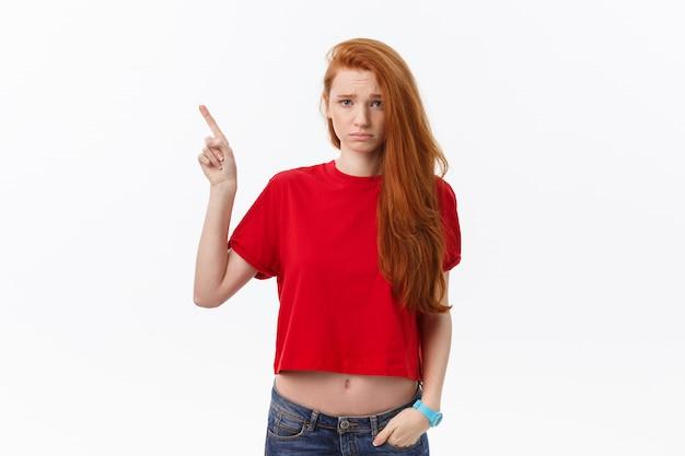 Макрофотография серьезной строгой молодой женщины носит красную рубашку выглядит подчеркнул и указывая пальцем, изолированных на белый