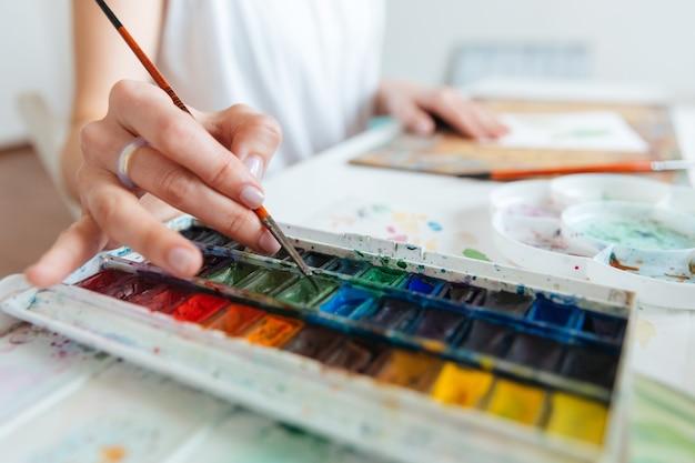 Крупным планом набор акварельных красок, используемых художницей на столе в мастерской
