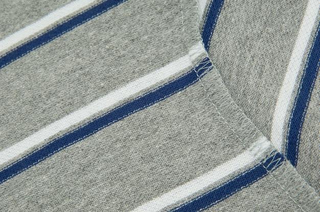 灰色の縞模様の生地に縫い目を縫うクローズアップ