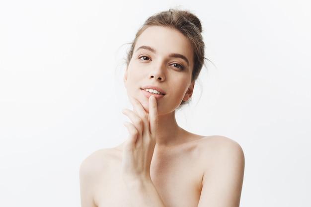 お団子の髪型と半分裸の体が笑顔でセクシーで見栄えの良い若いヨーロッパの黒髪の女性のクローズアップ、指で唇を優しく触れ、セクシーで魅力的な表情。