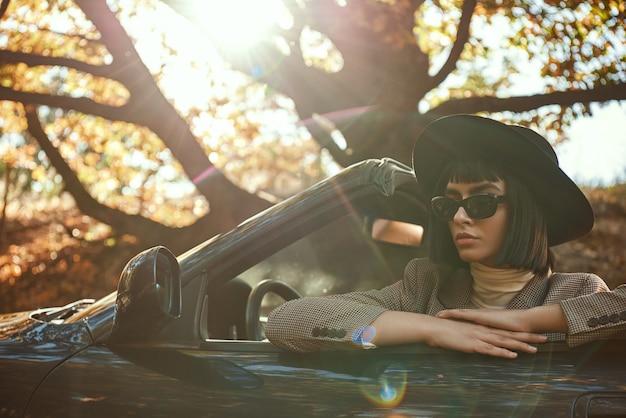 サングラスと帽子のセクシーな女性のクローズアップはカブリオレに座っています