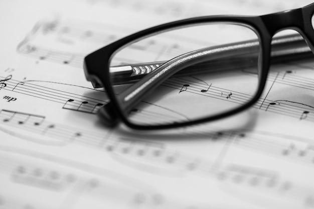 楽譜と眼鏡のクローズアップ。セレクティブフォーカスのある音符。