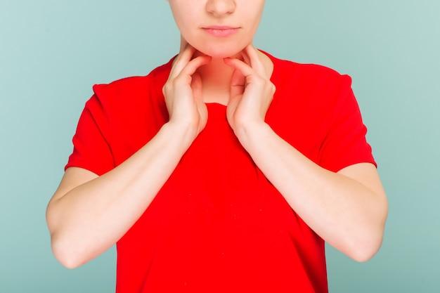 Крупным планом больная женщина с болью в горле плохо себя чувствует, страдает от болезненного глотания. красивая девушка касаясь шеи рукой. болезнь, здравоохранение и концепции медицины. высокое разрешение