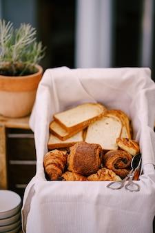 Крупным планом нарезанные булочки и круассаны в корзине для хлеба