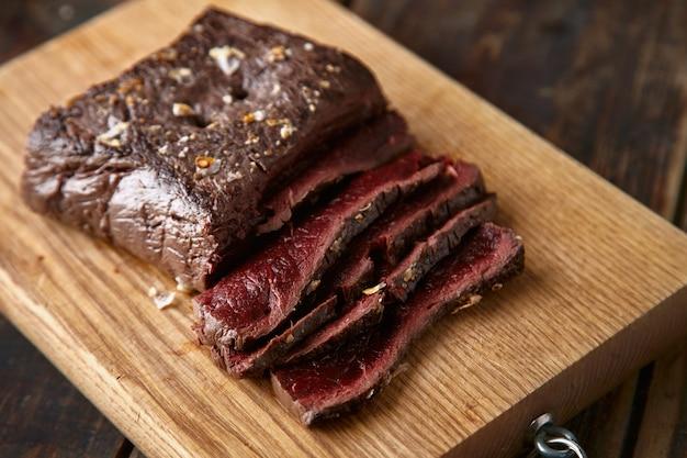 슬라이스 중간 희귀 요리 고래 고기 스테이크 나무 테이블의 근접 촬영