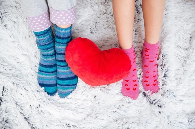 Крупным планом стройные красивые ножки двух молодых женщин в ярких носках на ковре