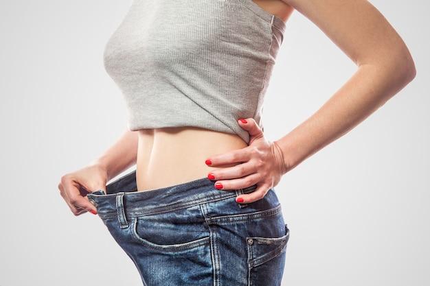 Крупным планом тонкая талия молодой женщины, стоящей в больших джинсах и сером топе, показывающей успешный вес