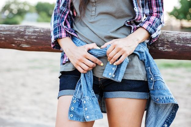 屋外に立っているジーンズのショートパンツでスリムな若い女性のクローズアップ