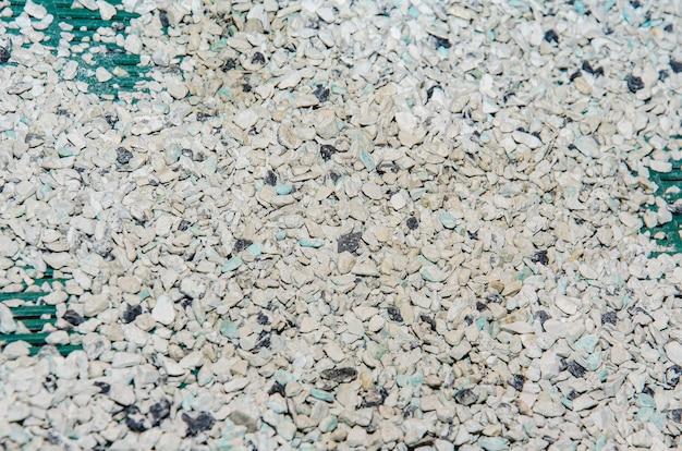 Крупный план небольших маленьких серых бежевых синих сломанных скал щебня, лежащих на земле.