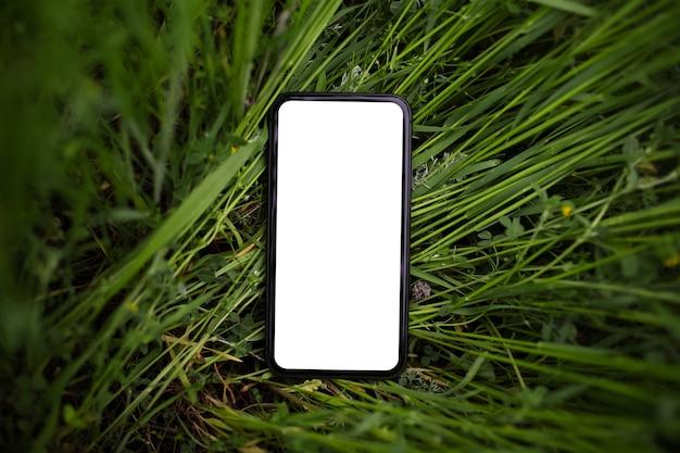 緑の芝生にモックアップを付けたスマートフォンのクローズアップ。上面図。自然な背景。