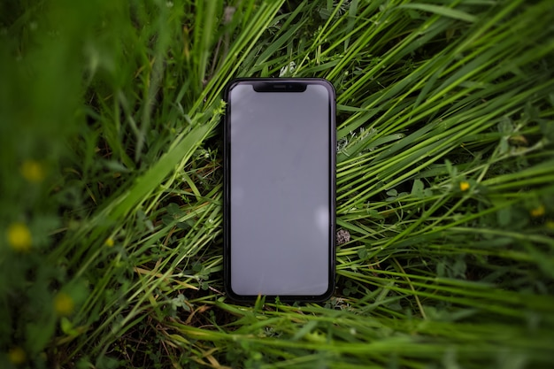 緑の芝生にモックアップを付けたスマートフォンのクローズアップ。上面図。