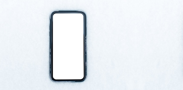 雪の背景にモックアップを付けたスマートフォンのクローズアップ。パノラマ バナー トップ ビュー。スペースのコンセプトをコピーします。