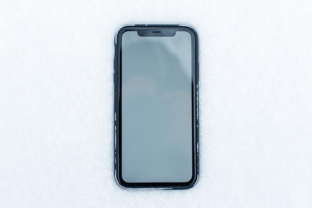 雪の背景にモックアップを付けたスマートフォンのクローズアップ。上面図。