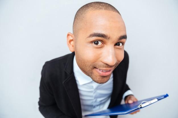 클립 보드를 들고 웃는 재미있는 아프리카 계 미국인 젊은 남자의 근접 촬영