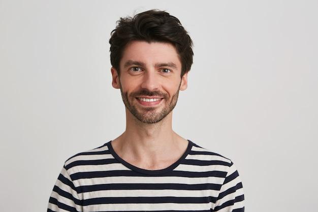 笑顔の魅力的なひげを生やした若い男のクローズアップは、白で隔離の幸せな感じの縞模様のtシャツを着ています