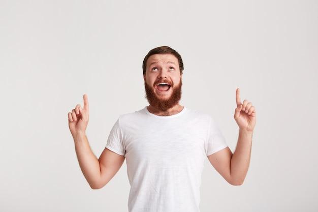 笑顔の魅力的な若い男のヒップスターのひげを生やしたtシャツを着てのクローズアップは幸せを感じ、白い壁に隔離された指でコピースペースの側を指しています