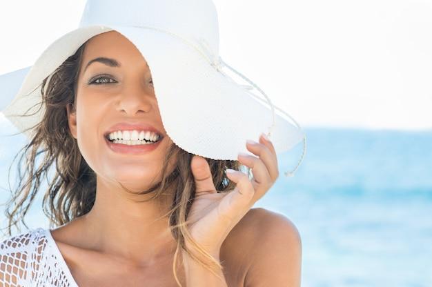 麦わら帽子とビーチで笑顔の美しい若い女性のクローズアップ