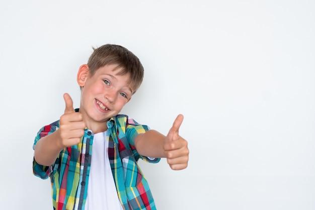 Крупный план усмехаясь мальчика показывая большой палец руки вверх жест изолированный на белой стене, космосе экземпляра.