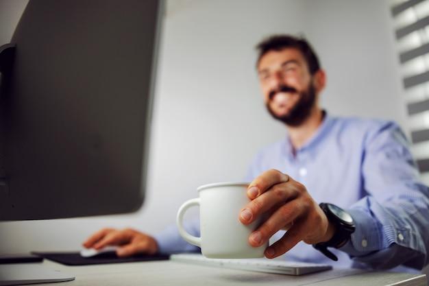 コンピューターを使用して彼のオフィスに座っている間コーヒーとマグカップを保持している笑顔のビジネスマンのクローズアップ。マグカップに選択的に焦点を当てます。