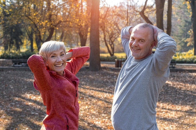 화창한 가을 날 공원에서 운동하는 웃고 있는 백인 노부부의 클로즈업