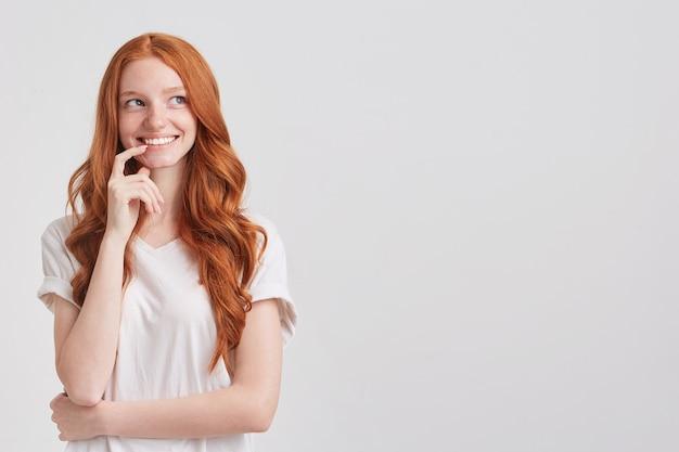 Крупным планом улыбающаяся прекрасная рыжая молодая женщина с длинными волнистыми волосами