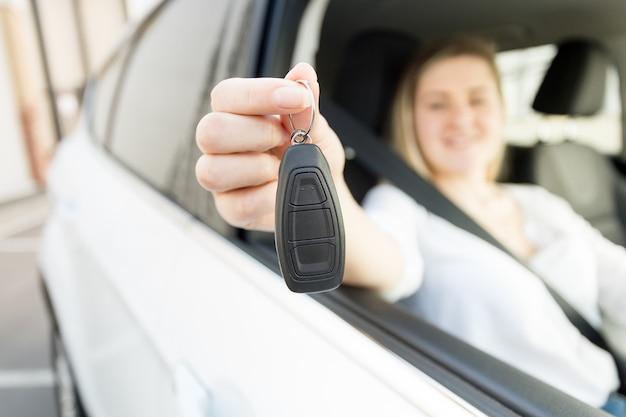 자동차 키를 들고 차를 운전하는 웃는 여자의 근접 촬영