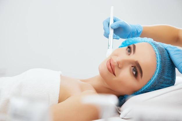Крупным планом улыбается женщина в синей кепке, лежа на диване в косметологической клинике. руки доктора в синих перчатках, касаясь ее лица кистью