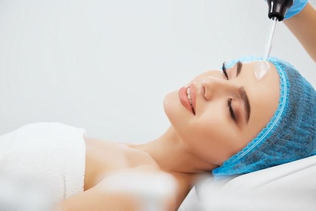 Крупным планом улыбается женщина в синей кепке, лежа на диване в косметологической клинике с закрытыми глазами. руки врача в синих перчатках делают процедуру дарсонвализации
