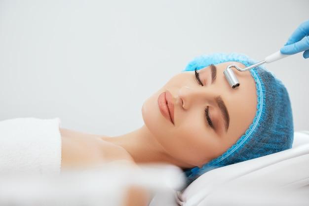 Крупным планом улыбается женщина в синей кепке, лежа на диване в косметологической клинике с закрытыми глазами. руки врача в синих перчатках делают процедуру с электродом для гальванизации