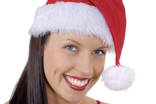 白い背景で隔離の赤いクリスマスサンタ帽子と笑顔の若い大人の女性のクローズアップ