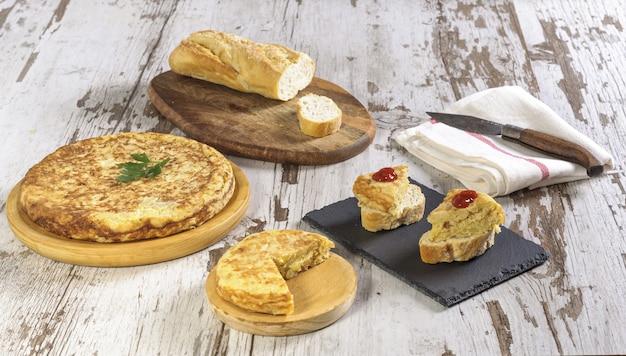 木製のテーブルの上のスペイン風オムレツとパンのクローズアップ