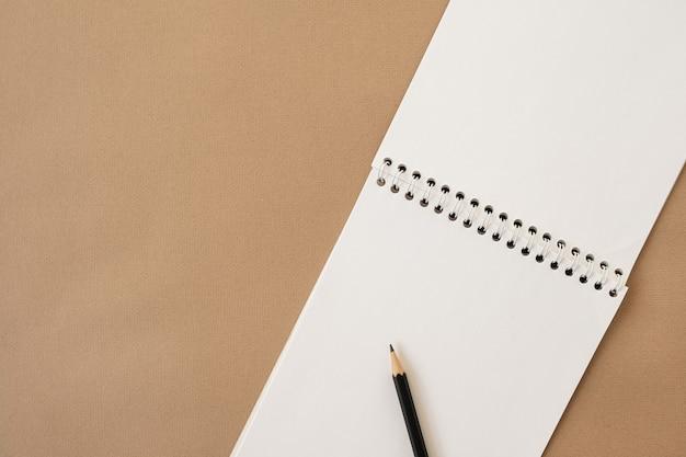 ニュートラルベージュのパステルカラーのスパイラルノートと鉛筆のクローズアップ。フラットレイ、上面図。