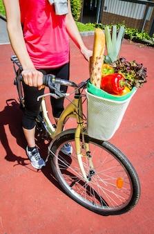 화창한 여름날 바구니 자전거에 식료품을 든 낚시를 좋아하는 여성의 근접 촬영