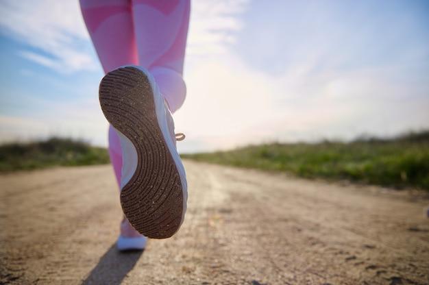 Крупный план спортивной обуви человека, бегущего по степной дороге с красивым солнечным светом. концепция кардио-тренировки на открытом воздухе. копировать пространство