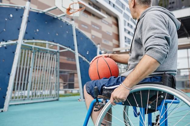 彼は屋外でバスケットボールをしている彼の手でボールを保持している車椅子のスポーツマンのクローズアップ