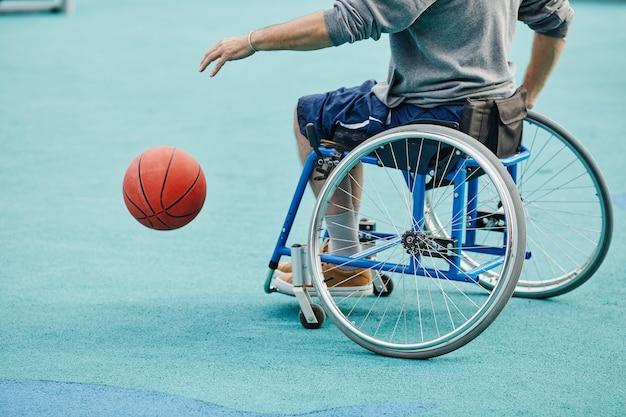屋外でバスケットボールをしている車椅子に座っている障害を持つスポーツ選手のクローズアップ